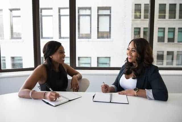 سيدتان تجلسان في مكان العمل تتعاملان بمرح وهذا من صفات برج الميزان