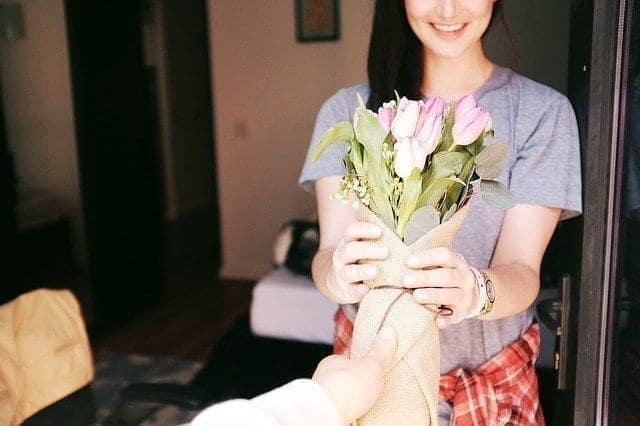رجل يقدم لسيدة باقة من الورد