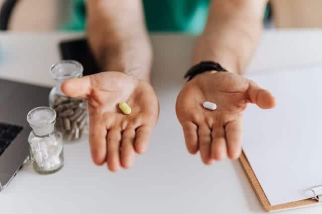 شخص يحمل نوعين من الدواء في يده