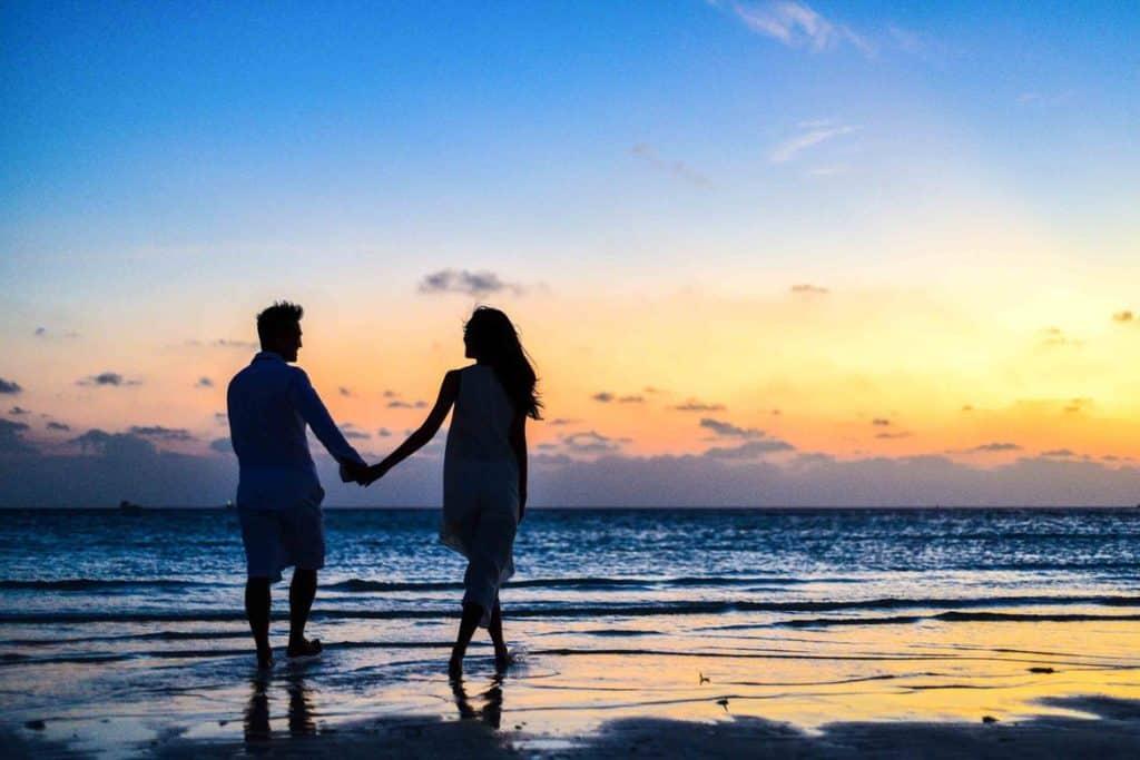 رجل وفتاة يسيران على شاطئ البحر