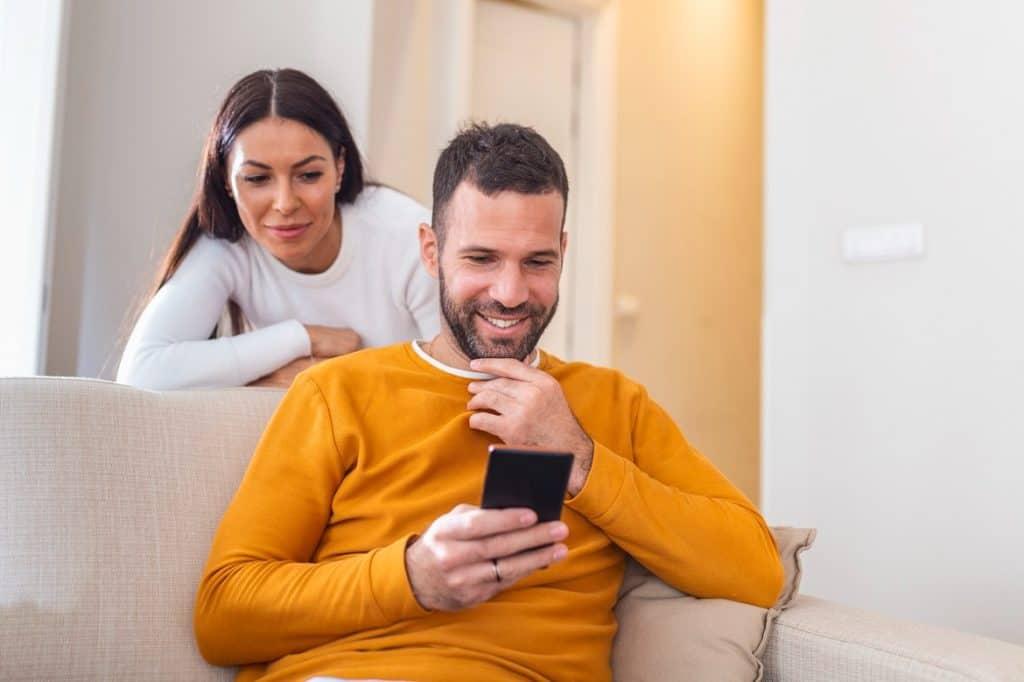 زوجة تنظر في هاتف زوجها